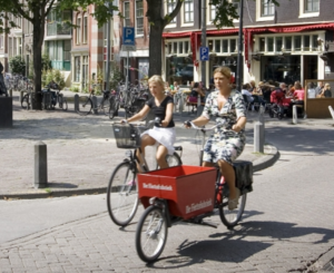 Two women ride their bicycles on the Lindengracht market in Amsterdam in August 2004. Credit: Michael Kooren/Reuters
