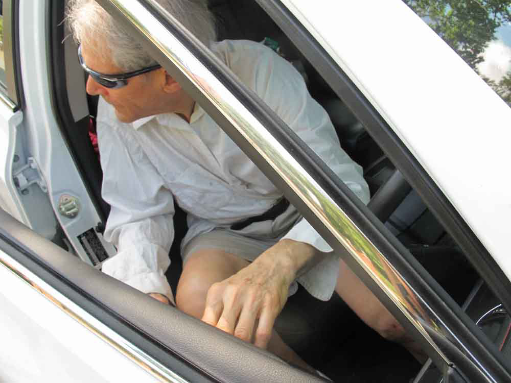 Older man using left (far hand) in Dutch Reach to open car door part way, looking back for on-coming bicycles or other traffic before fully opening to exit.