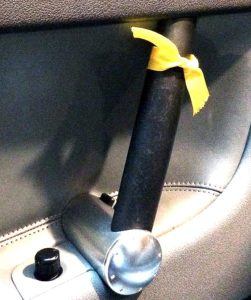 Ribbon tied to car door latch to remind driver or passenger to use Dutch Reach far hand habit to open car door and avoid injury of cyclist, getting oneself or door damage hit by traffic.