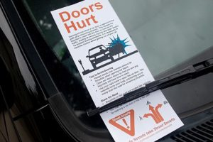 Driver reeducation flier placed under windshield wiper of parked cars, Orange St, New Haven, CT in 2013; advises 'Amsterdam method.'