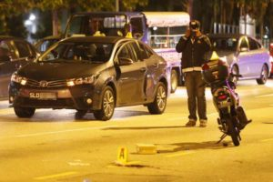 Crash scene of fatal dooring of motorcyclist on Singapore street after passenger opened car door into cyclist's path.