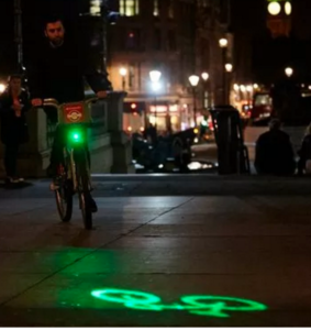 Night scene of cyclists beaming green image of a bicycle meters ahead onto pavement.