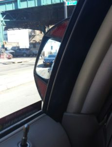 Thin vertical mirror attaches to post between front and back side windows for use by back seat occupants to watch out for bikes, trucks, cars, helps prevent, avoid doorings or being injured themselves.