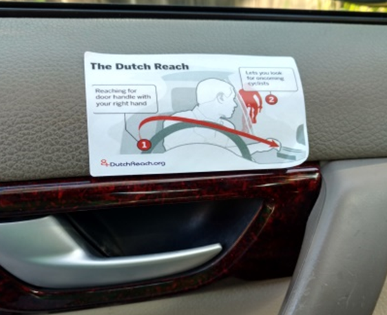 Boston Globe diagram on how to perform the Dutch Reach habit to avoid car doorings of cyclists by using far hand to reach across to unlock latch, forcing body to turn. This allows driver or passenger to swivel head to scan directly back to look for on-coming bicyclists or other traffic.