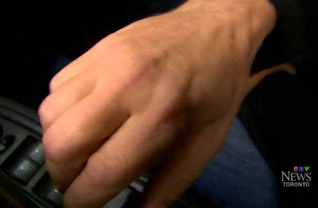 Image of a right hand on inside car door latch/ handle, doing the Dutch Reach anti dooring maneuver in a video produced by Canadian TV Toronto, October 13, 2016 explaining the Dutch Reach.