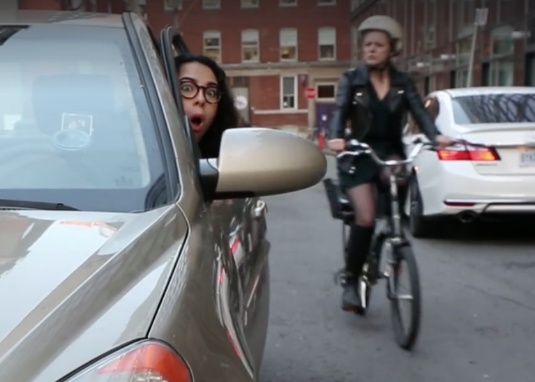 Huff Post video gag shot for We Aspire Facebook posting of video. Woman driver looking at side view mirror aghast to see oncoming woman cyclist.