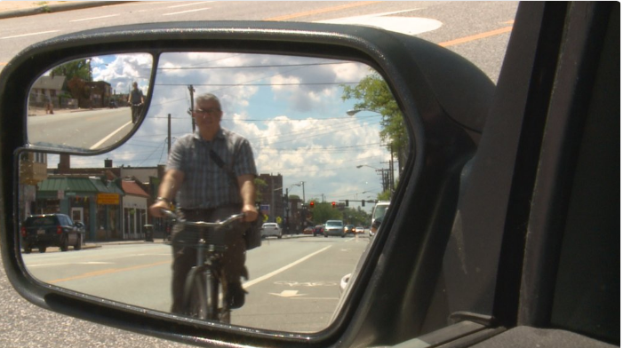 Cyclist viewed in left side mirror from WKYC Investigator news report on Doorings. Twitter image for Investigator | Bicyclists, car doors collide with painful results. July 10, 2017 WKYC Channel 3 News. Cleveland, OH, USA.