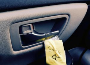 """A note is taped next to car door latch with arrow pointing to latch & word """"Look"""" printed on it. Note is to remind driver or passenger to use the safer far hand Dutch Reach method to exit vehicle to avoid dooring a cyclist who might otherwise crash into or hit the door were it suddenly opened."""
