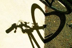 Photo: Bike shadow on wall and adjacent ground, shows hand bars, stem, front wheel & fork. Shadow of wheel bends at ground, forming heart shaped front wheel shadow.  Unknown photographer, found on Google search of bike + heart