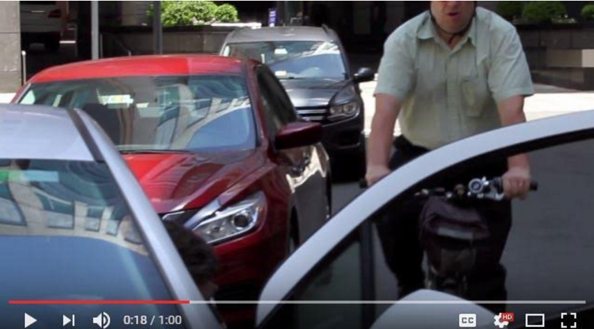 "Screen shot of cyclist in door zone or bike lane along side parallel parked cars, approaches an opened car door. Caption reads: ""A scene from MassDOT's Dutch Reach video depicting the moment before a ""dooring"" incident; these collisions can result in serious injury or death, and are one of the most prevalent dangers to cyclists everywhere."" Taken from a Massachusetts DOT /  RMV YouTube video produced"