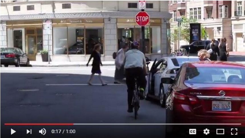 "Screen shot from Massachusetts RMV / DOT driver & bicycle safety video on Dutch Reach method. Photo shows cyclist riding along side parked cars. Caption reads: ""Because it is difficult for a cyclist to see if there is a driver in each individual car, doors that open in front of their paths can be totally unexpected and forcing the bicyclist to stop on a dime."""