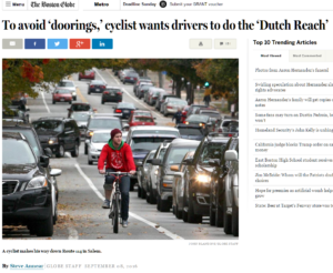 Photo of a  young man cyclist riding on heavily traffic'd street in Salem, MA, USA, no helmet, wearing red jacket.