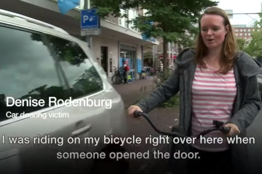 Young woman walks her bicycle beside a parked car, tells how she was doored, injured - follows video re-enactment of her crash / accident hitting carelessly opened car door. This sets up the short educational video How to do the Dutch Reach by the Royal Society for the Prevention of Accidents UK.